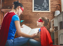 Meisje en mamma in Superhero-kostuum stock foto
