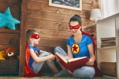 Meisje en mamma in Superhero-kostuum royalty-vrije stock foto's