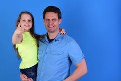 Meisje en mens met gelukkige gezichten op blauwe achtergrond Stock Foto's