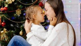 Meisje en moeder die binnen met Kerstmisboom koesteren op de achtergrond Royalty-vrije Stock Foto