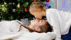 Meisje en moeder die binnen met Kerstmisboom koesteren op de achtergrond Stock Afbeelding