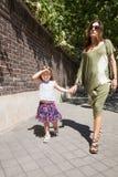 Meisje en moeder die hand in hand op de straat lopen Stock Foto's