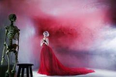 Meisje en skelet het conceptenleven of dood De foto van de manier van jonge prachtige vrouw in rode kleding Geweven Achtergrond stock afbeelding