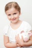 Meisje en spaarvarken Stock Foto's