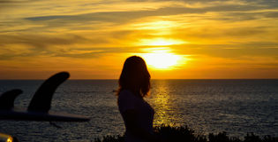 Meisje en surfplank bij zonsondergang royalty-vrije stock afbeeldingen