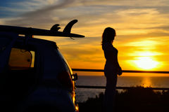 Meisje en surfplanksilhouetten bij zonsondergang stock afbeeldingen