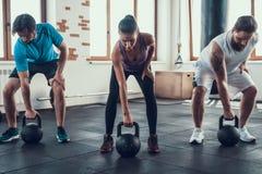 Meisje en Twee Kerels die Gewichten in Geschiktheidsclub opheffen stock foto's