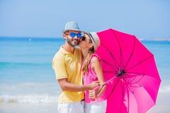 Meisje en vader met een roze paraplu op het zandige strand stock foto