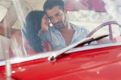 Meisje en vriend die in rode oude auto flirten royalty-vrije stock fotografie