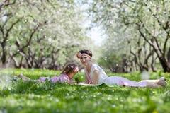 Meisje en vrouw in de de lentetuin Stock Foto's