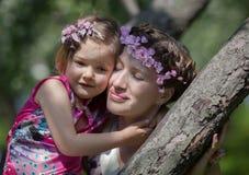Meisje en vrouw in de de lentetuin Stock Afbeelding