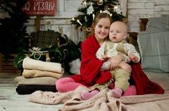 Meisje en weinig broerzitting op een deken Stock Afbeeldingen