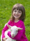 Meisje en weinig geitzitting op een weide royalty-vrije stock fotografie