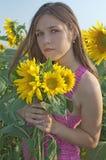 Meisje en zonnebloemen Stock Foto's