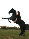 Meisje en zwart paard stock afbeelding