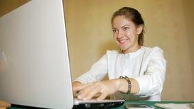 Meisje freelancer door twee handen die zeer snel op laptop en de blikken zeer actief bij de monitor typen De jonge vrouw stock video