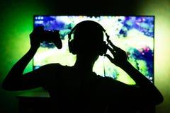 Meisje gamer in hoofdtelefoons in dark op TV-achtergrond Capaciteit om als achtergrond te gebruiken Silhouet royalty-vrije stock fotografie