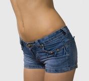 Meisje in geïsoleerde jeans korte borrels Stock Foto