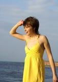 Meisje in geel op een bank van de rivier Royalty-vrije Stock Afbeelding