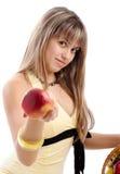 Meisje in gele kleding die een appel geeft stock afbeelding