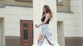 Meisje in gescheurde jeans en t-shirt die in de de zomerstad lopen en aan muziek op hoofdtelefoons luisteren Langzame Motie stock videobeelden