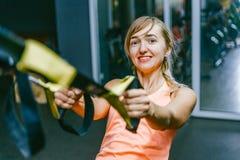 Meisje in geschiktheidszaal met lijnen sporten die scharnieren TPX opleiden Sterkte opleiding, opschorting opleiding strapping On Stock Afbeelding