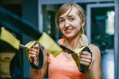 Meisje in geschiktheidszaal met lijnen sporten die scharnieren TPX opleiden Sterkte opleiding strapping Ontwikkeling van de vesti Stock Afbeeldingen