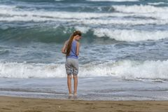 Meisje in gestreepte t-shirt die langs het strand lopen royalty-vrije stock foto's