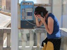 Meisje gesturing droevig op een openbare payphone cabine Royalty-vrije Stock Afbeeldingen