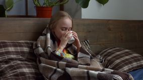 Meisje gevangen griep en het drinken hete thee in bed stock videobeelden