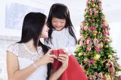 Meisje geven huidig bij Kerstmisdag Stock Foto's