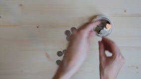 Meisje gezette muntstukken in kruik stock video