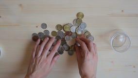 Meisje gezette muntstukken in kruik stock videobeelden