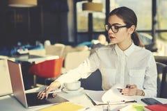 Meisje in glazen die makend statistieken en hoeveelheid kosten die moderne technologieën gebruiken werken royalty-vrije stock afbeeldingen