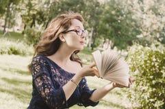 Meisje in glazen die op de pagina's van een boek blazen Royalty-vrije Stock Afbeelding