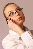 Meisje in glazen en met een mobiele telefoon Stock Foto's