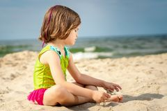 Meisje in groene zwempakzitting op het zand bij het strand stock afbeeldingen