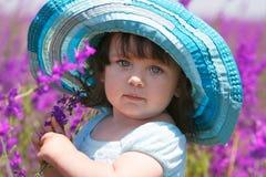 Meisje in grote blauwe hoed op natuurlijke achtergrond Stock Afbeelding