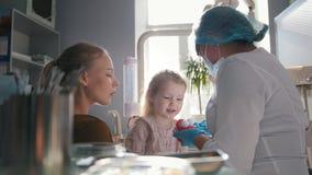 Meisje, haar mamma en tandarts in het en, dochter tandbureau, stomatologist die spelen raadplegen onderzoeken en stock footage