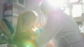 Meisje, haar mamma en tandarts in het tandbureau, stomatologist die een speciaal stuk speelgoed raadplegen stock video