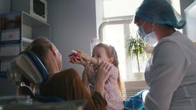 Meisje, haar mamma en tandarts in het tandbureau, stomatologist die met een speciaal stuk speelgoed adviseren stock footage