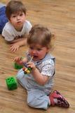 Meisje haar nieuw stuk speelgoed proeven en jongen die curiosly terug liggen Stock Afbeeldingen