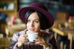 Meisje in in hand kop van de Koffieholding van hete koffie, het glimlachen stock foto