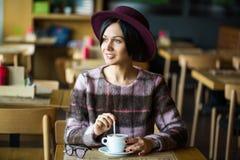 Meisje in in hand kop van de Koffieholding van hete koffie, het glimlachen stock afbeeldingen