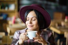 Meisje in in hand kop van de Koffieholding van hete koffie, het glimlachen royalty-vrije stock foto's