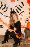Meisje in heksenkostuum op Halloween op de pompoen stock afbeelding