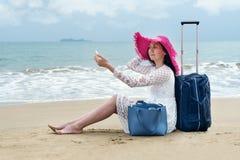 Meisje in heldere hoedenzitting op het strand stock afbeeldingen
