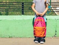 Meisje in heldere kleren en tennisschoenen met een roze rugzak tegen een groene muur Het concept van de school Horizontaal kader stock foto's