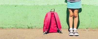Meisje in heldere kleren en tennisschoenen met een roze rugzak tegen een groene muur Het concept van de school Horizontaal kader royalty-vrije stock fotografie