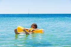 Meisje het baden met een vlotter op het strand royalty-vrije stock fotografie
